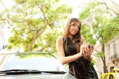 Mulher de negócios que inclina-se no carro com smartphone. Fotos de Stock