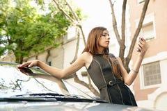 Mulher de negócios que inclina-se no carro com smartphone. imagens de stock royalty free
