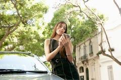 Mulher de negócios que inclina-se no carro com smartphone. Foto de Stock Royalty Free