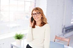Mulher de negócios atrativa que faz uma chamada ao estar no escritório foto de stock