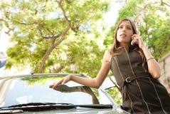 Mulher de negócios que inclina-se no carro com smartphone. fotografia de stock royalty free