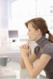 Mulher de negócios atrativa que pensa na mesa imagem de stock