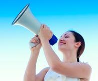 Mulher de negócios atrativa que shouting em um megafone imagem de stock