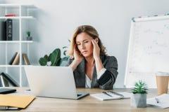 mulher de negócios atrativa que tem a dor de cabeça e que olha o portátil foto de stock