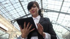 Mulher de negócios atrativa que usa uma tabuleta digital ao estar na escada rolante em um prédio de escritórios filme