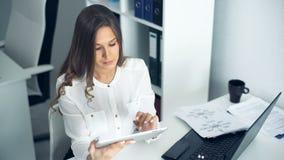 Mulher de negócios atrativa que usa uma tabuleta digital no escritório video estoque