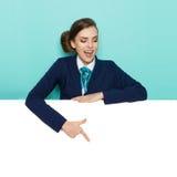 Mulher de negócios Behind Placard Is que aponta e que fala Fotografia de Stock Royalty Free
