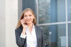 Mulher de negócios bem sucedida que fala no telefone celular ao andar exterior fotos de stock royalty free