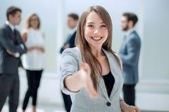Mulher de negócios bem sucedida que guarda para fora sua mão para um aperto de mão fotografia de stock