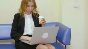 Mulher de negócios bonita com o café para ir trabalhar no portátil ao sentar-se no sofá filme