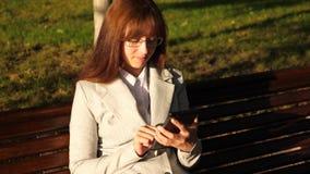 A mulher de negócios bonita da mulher com vidros verifica o e-mail na tabuleta no parque em um banco video estoque