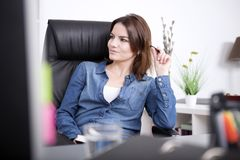 Mulher de negócios bonita na sarja de Nimes que senta-se na cadeira Imagem de Stock