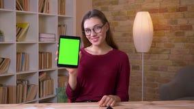 A mulher de negócios bonita nos vidros mostra a tela verde alegremente vertical da tabuleta para recomendar o app no escritório filme