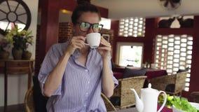Mulher de negócios bonita nos vidros que bebe o chá e que relaxa no café vídeos de arquivo