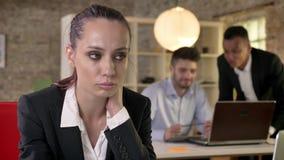 A mulher de negócios bonita nova é virada sobre seus colegas dos homens na bisbolhetice do fundo sobre o herm, conceito do sexism filme