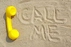 mulher de negócios bonita nova em um fundo isolado A tubulação amarela de um telefone velho do vintage encontra-se na areia imagens de stock royalty free
