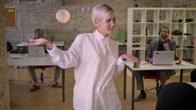 A mulher de negócios bonita nova está dançando no escritório, colegas está aplaudindo, trabalha o conceito, relaxa o conceito vídeos de arquivo