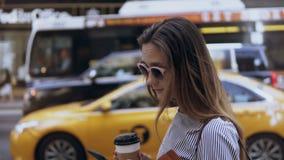 Mulher de negócios bonita nova que está perto da estrada, do café bebendo e usando o smartphone Táxi de espera fêmea video estoque