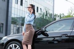 Mulher de negócios bonita nova que fala na parte externa e na inclinação do smartphone fotografia de stock