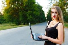 Mulher de negócios bonita nova que guarda o portátil na estrada Imagem de Stock Royalty Free