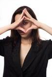 Mulher de negócios bonita nova que olha através do quadro de seus dedos foto de stock royalty free