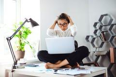 Mulher de negócios bonita nova que senta-se na tabela com o portátil no local de trabalho Imagem de Stock