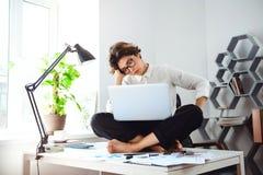 Mulher de negócios bonita nova que senta-se na tabela com o portátil no local de trabalho Fotografia de Stock Royalty Free