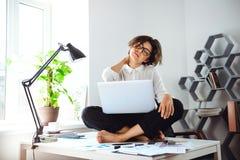 Mulher de negócios bonita nova que senta-se na tabela com o portátil no local de trabalho Imagens de Stock