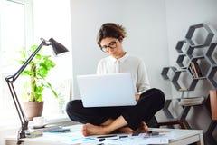 Mulher de negócios bonita nova que senta-se na tabela com o portátil no local de trabalho Foto de Stock