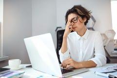 Mulher de negócios bonita nova que trabalha com o portátil no local de trabalho no escritório Imagem de Stock