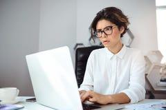 Mulher de negócios bonita nova que trabalha com o portátil no local de trabalho no escritório Fotos de Stock Royalty Free