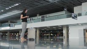 Mulher de negócios bonita nova Using Smartphone no aeroporto ao esperar sua fila pelo registro, conceito de viagem Fotos de Stock Royalty Free