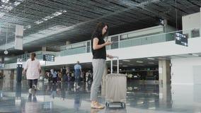 Mulher de negócios bonita nova Using Smartphone no aeroporto ao esperar sua fila pelo registro, conceito de viagem Fotos de Stock
