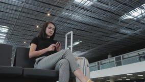 Mulher de negócios bonita nova Using Smartphone no aeroporto ao esperar sua fila pelo registro, conceito de viagem Imagens de Stock