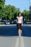 Mulher de negócios bonita que anda na estrada Foto de Stock