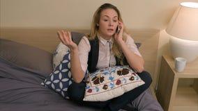 Mulher de negócios bonita que discute muito irritado no telefone que senta-se na cama em casa Imagens de Stock Royalty Free