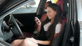 Mulher de negócios bonita que envia um texto ao assentar no carro com cadeiras vermelhas, menina nova da classe executiva do estu Imagem de Stock Royalty Free