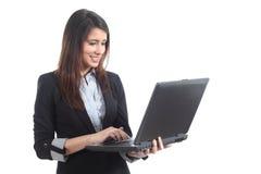 Mulher de negócios bonita que está de dactilografia em um portátil Foto de Stock Royalty Free
