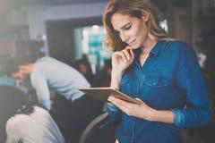 Mulher de negócios bonita que guarda a tabuleta no escritório moderno fotos de stock royalty free