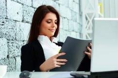 Mulher de negócios bonita que lê o caderno Imagem de Stock