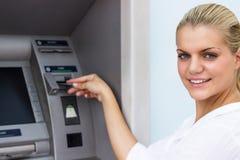 Mulher de negócios bonita que retira o dinheiro do cartão de crédito imagem de stock royalty free