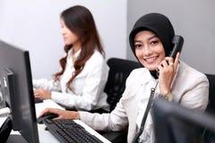 Mulher de negócios bonita que sorri ao responder ao telefone imagens de stock