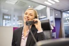 Mulher de negócios bonita que telefona em seu escritório imagens de stock royalty free