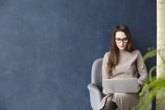 Mulher de negócios bonita que trabalha no portátil ao sentar-se no escritório moderno do sótão Escuro - fundo azul da parede, luz
