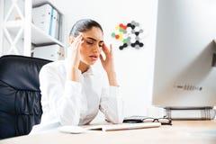 Mulher de negócios cansado que tem uma dor de cabeça ao sentar-se na mesa imagens de stock
