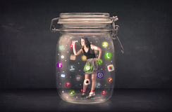 A mulher de negócios capturou em um frasco de vidro com ícones coloridos c do app Imagem de Stock