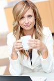 Mulher de negócios carismática que prende uma chávena de café Foto de Stock