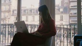 Mulher de negócios caucasiano bonita bem sucedida feliz que usa o portátil que sorri na janela bonita do hotel de Paris em férias vídeos de arquivo