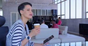 Mulher de neg?cios caucasiano bonita que usa a tabuleta digital ao beber o caf? no escrit?rio moderno 4k filme