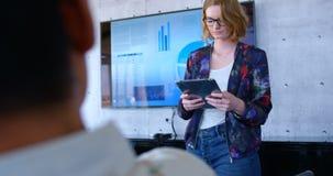 Mulher de negócios caucasiano bonita que usa a tabuleta digital no escritório moderno 4k video estoque